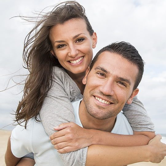 couple smiling at beach (edited)
